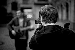 Julian Höcher nimmt Georg Weiss auf, während dieser Gitarre spielt und Sing