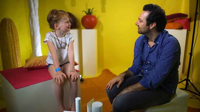 Ein kleines Mädchen und ein Mann sitzen in einem zimmer. Beide Lächeln sich an.