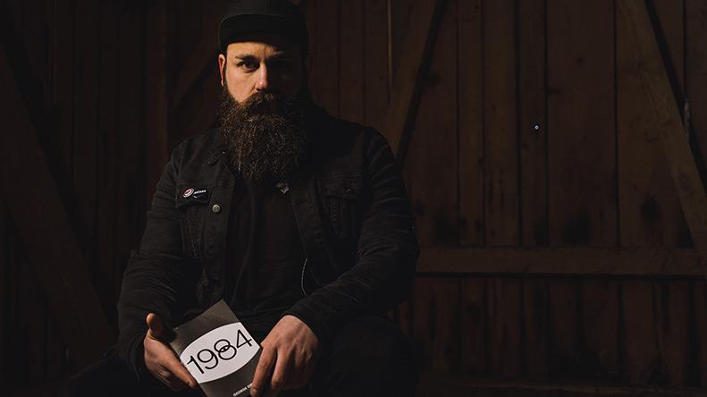 Ein Mann mit langem Bart und schwarzer Jacke sitzt in einer Scheune